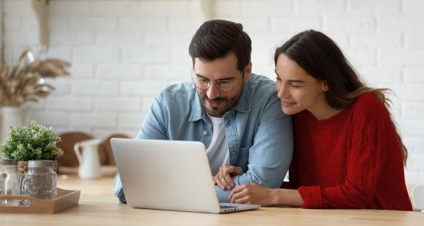 pleasant family couple sitting before laptop