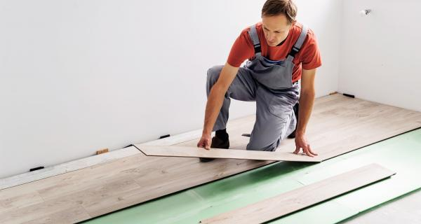 man in overalls laying down laminate flooring